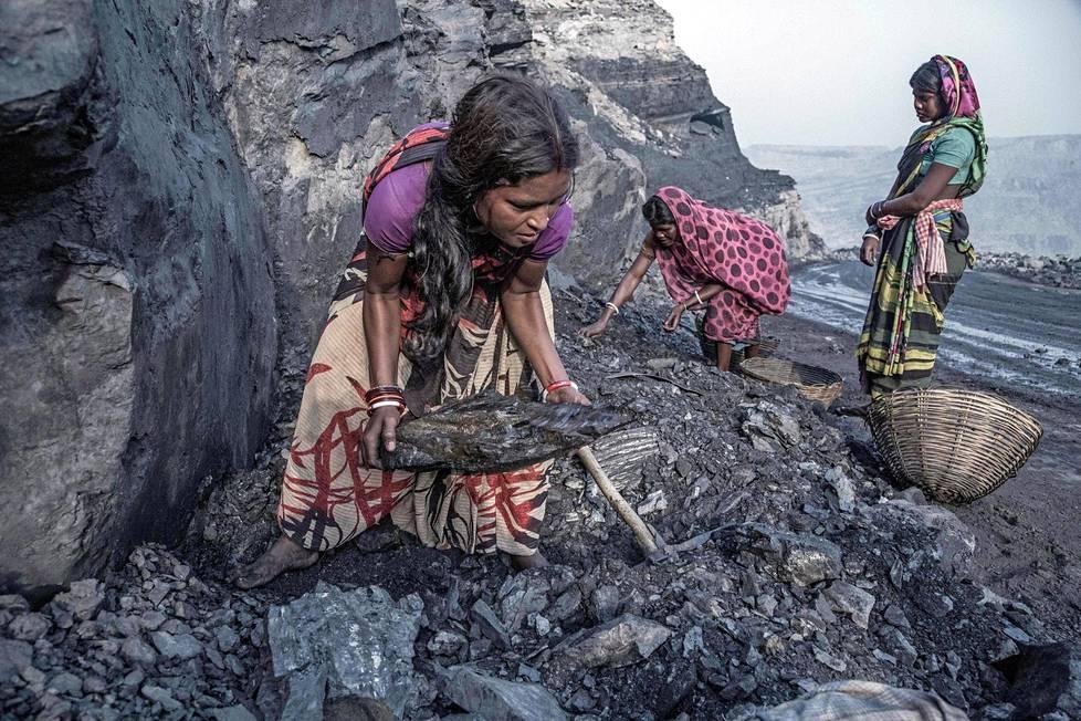 Nuoret tytöt täyttivät korejaan hiilenpalasilla Jharian kaivosten avolouhoksella.