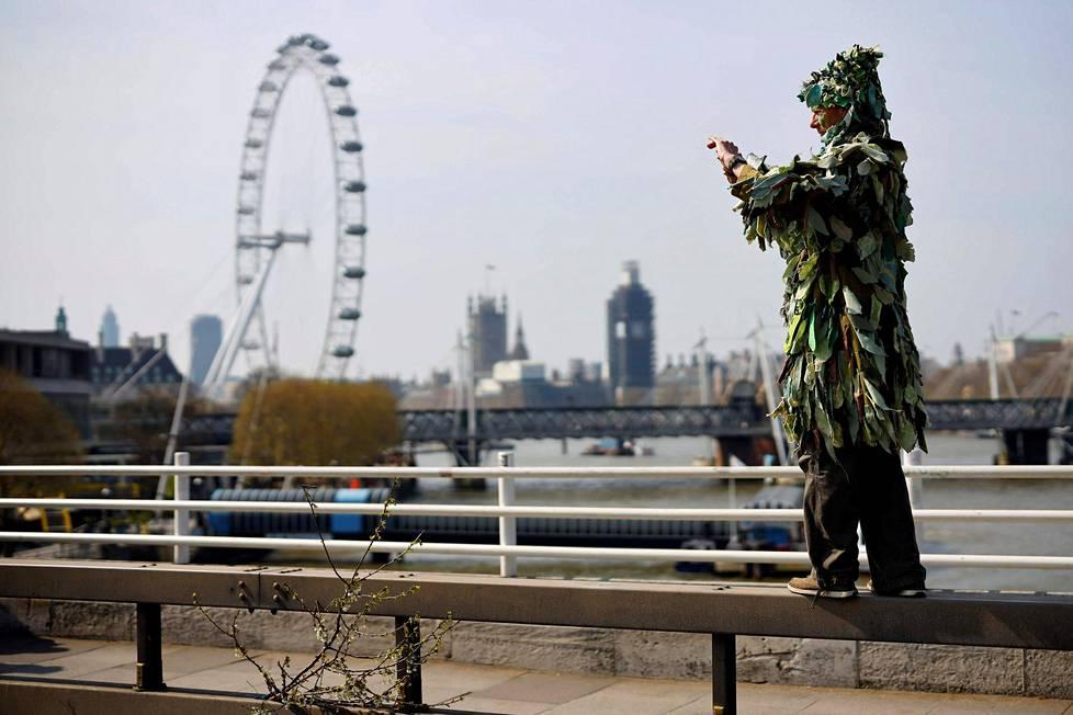 Kasvillisuudeksi pukeutunut mielenosoittaja Waterloon sillalla.