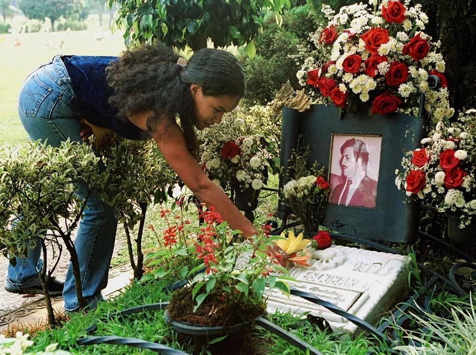 Nainen laittoi kukkia Pablo Escobarin haudalle vuonna 2000.