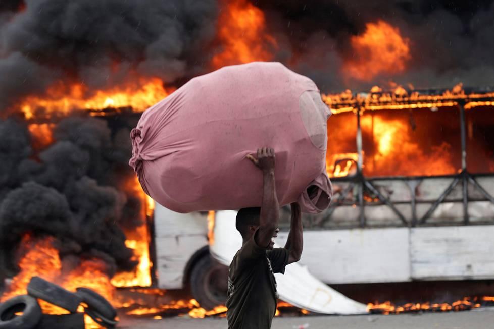Bisnes on tärkeintä. Haitilaismies kantoi muina miehinä kaupustelutavaroitaan palavan bussin editse maan pääkaupungissa Port-au-Princessa. Maassa on osoitettu rajusti mieltä hallitusta vastaan.