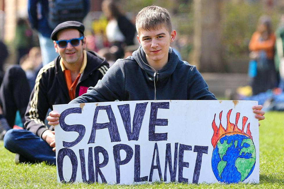 """""""Pelastakaa planeettamme"""", pyysi kyltissään parlamenttitalon aukiolla istunut nuorukainen."""
