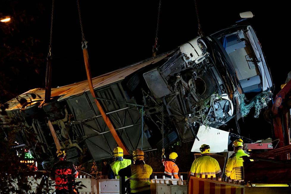 Pahoin vaurioitunut bussi laskettiin lavettiauton lavalle.