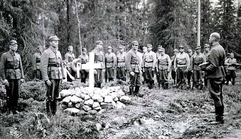 Surmapaikalle pystytettiin nopeasti valkoinen risti, joka myöhemmin korvattiin muistokivellä ja laatalla. Kuvasta näkyy, kuinka tiheä vaijytyskuusikko oli vuonna 1942.