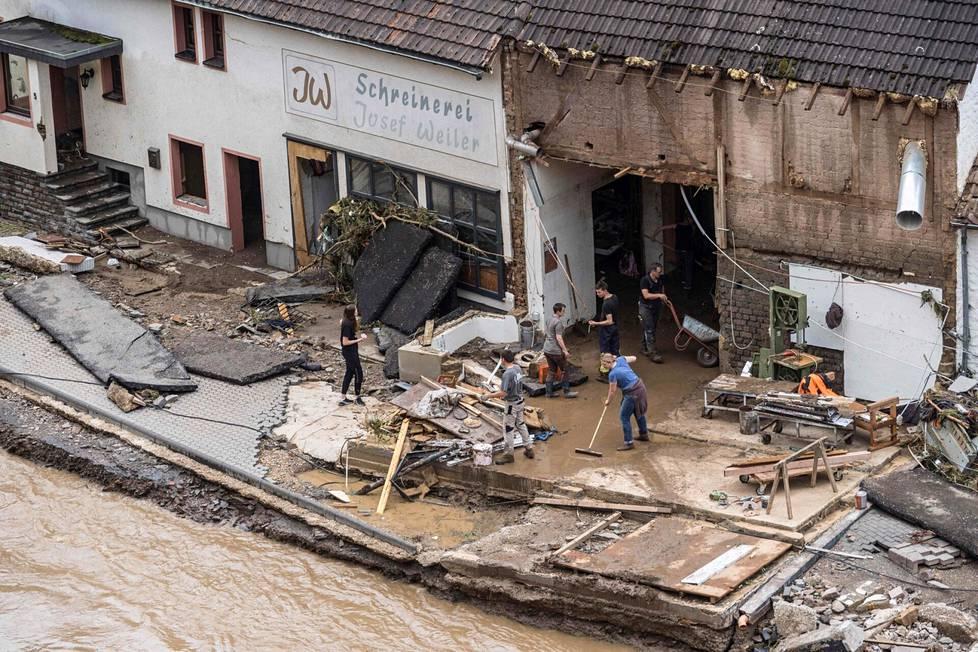 Ihmisiä poistamassa tulvavettä tuhoutuneesta asunnosta Schuldissa läntisessä Saksassa.