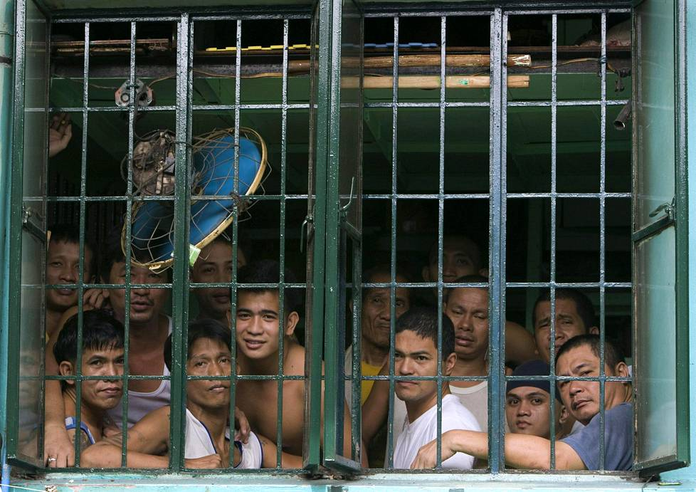 Vangit katsovat täpötäyden sellin ikkunasta ulos arkistokuvassa.