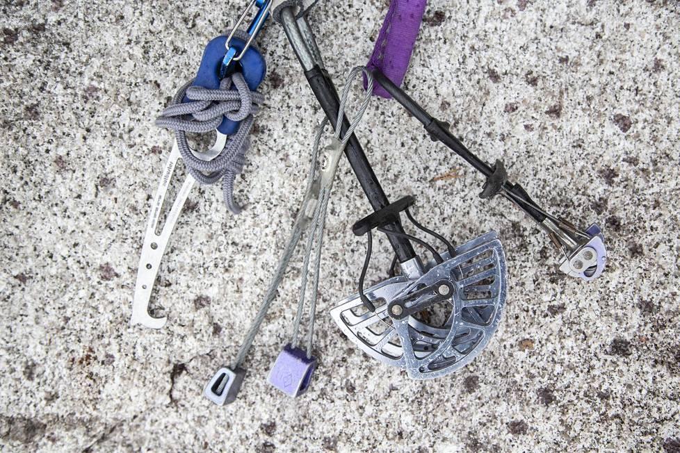 Kiipeilyssä tarvittavia varusteita. Vasemmalla kiila-avain ja oikealla kaksi Camalotia, eli tuttavallisemmin camua. Keskellä kaksi kiilaa. Kiiloja ja camuja työnnetään kallion koloihin ja ne pysäyttävät mahdollisen putoamisen.