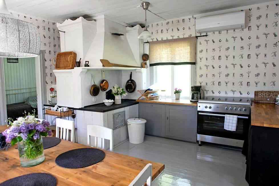 Keittiössä on valkoinen leivinuuni huuvineen, mutta myös moderni liesi ja uuni.
