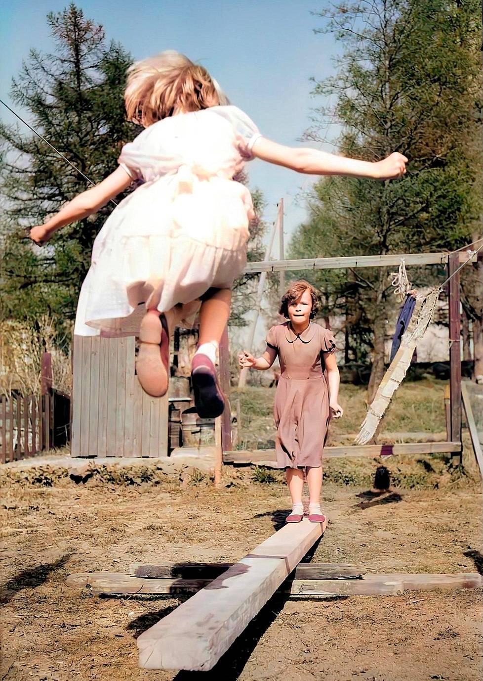 Tytöt pomppivat hyppylaudalla Intiankadulla 1957. Onkohan kevätjuhlapäivä, kun heillä on noin hienot mekot yllään?