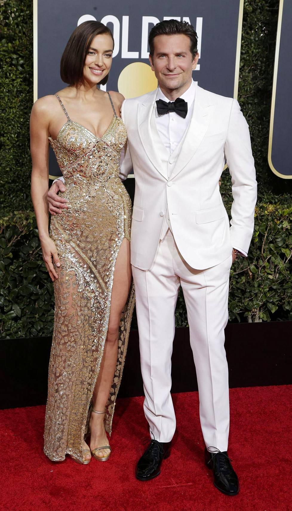 Huippumalli Irina Shayk miehensä Bradley Cooperin kanssa. Shayk'n kullanhohtoisen luomuksen halkio kipusi korkealle, Cooper taas valitsi ylleen valkoista.