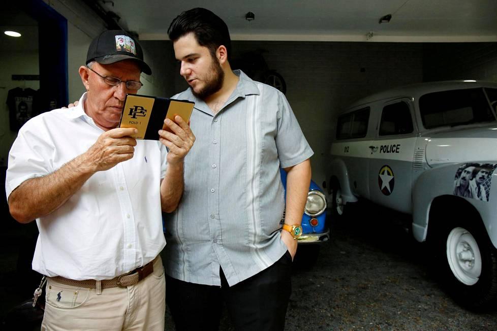 Escobarin veli Roberto (vas.) ja Escobar Incin pomo Olof Gustafsson tutkivat firmansa taitettavaa puhelinta.