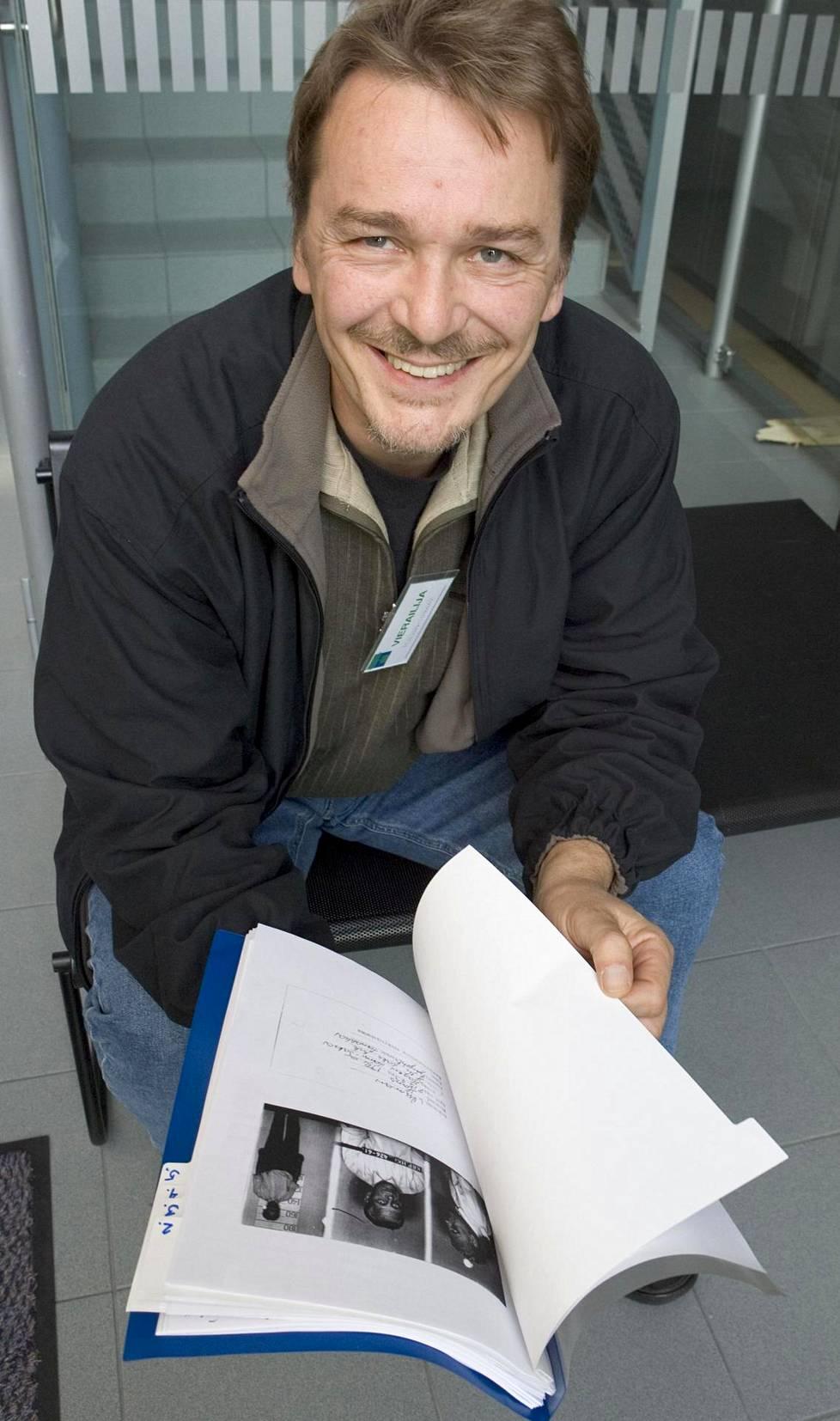 Mika Mölsä lukemassa keskusrikospoliisin Assman-kansiota. Mölsä kuoli vuonna 2011.
