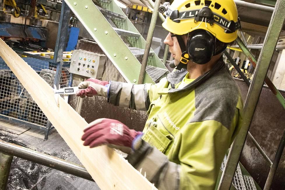 Sahatyömies Jari Kyröläinen tarkistaa työntömitalla, että ensimmäisenä sahatut sivulaudat ovat mitassaan.