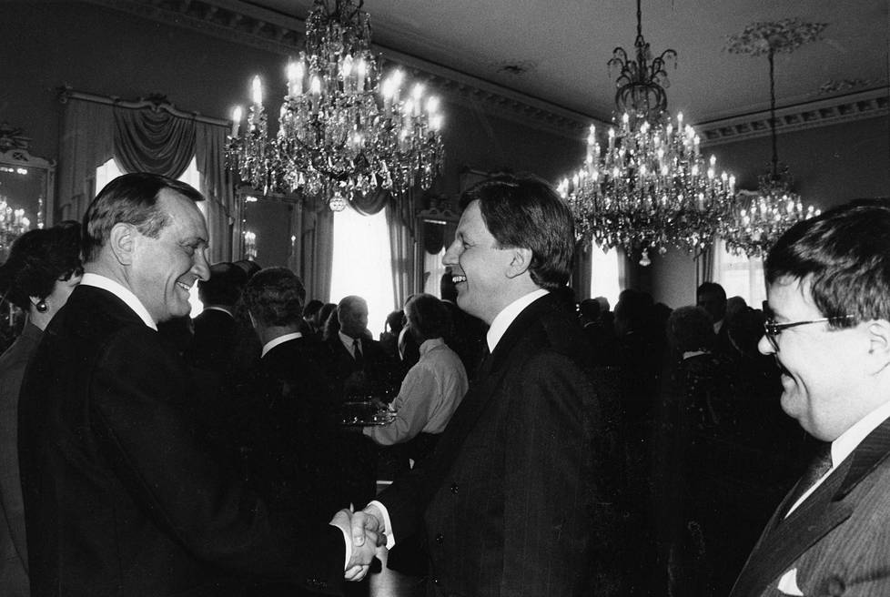 Vallanvaihto YYA-juhlassa. Vasemmalla väistyvä pääministeri Harri Holkeri, keskellä tuleva, Aho. Oikealla kurkistaa maa- ja metsätalousministeri Ole Norrback.