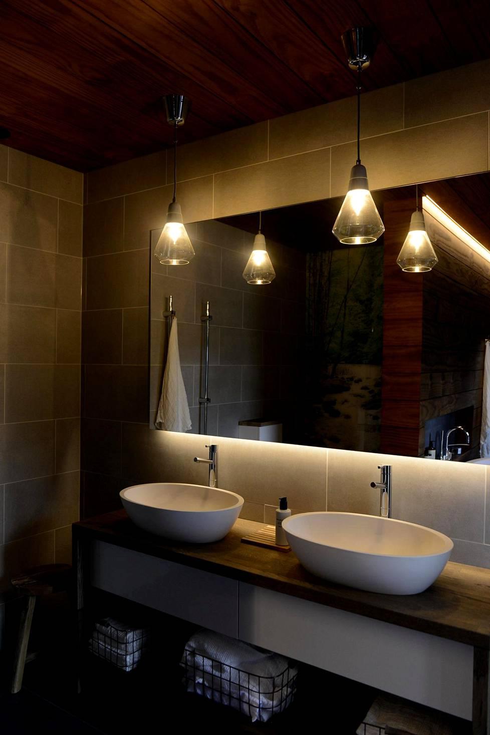 Useissa kohteissa kylpyhuoneen valaistukseen oli haettu vaihtelua riippuvilla valaisimilla.