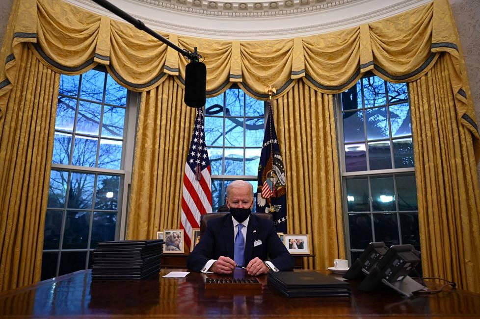 Presidentti Joe Biden ensimmäistä kertaa virkapöytänsä takana Valkoisessa talossa.