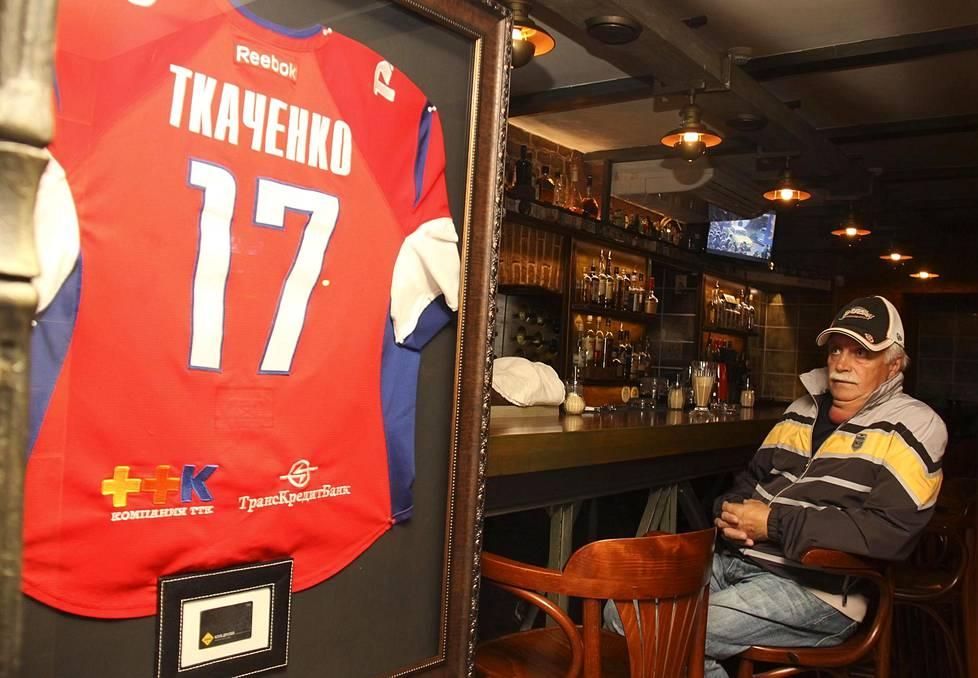 Ivan Tkatshenkon isä Leonid katselee poikansa pelipaitaa baarissa, jonka Ivan omisti. Kuppila avattiin Jaroslavliin keväällä 2011, vain muutama kuukausi ennen onnettomuutta.