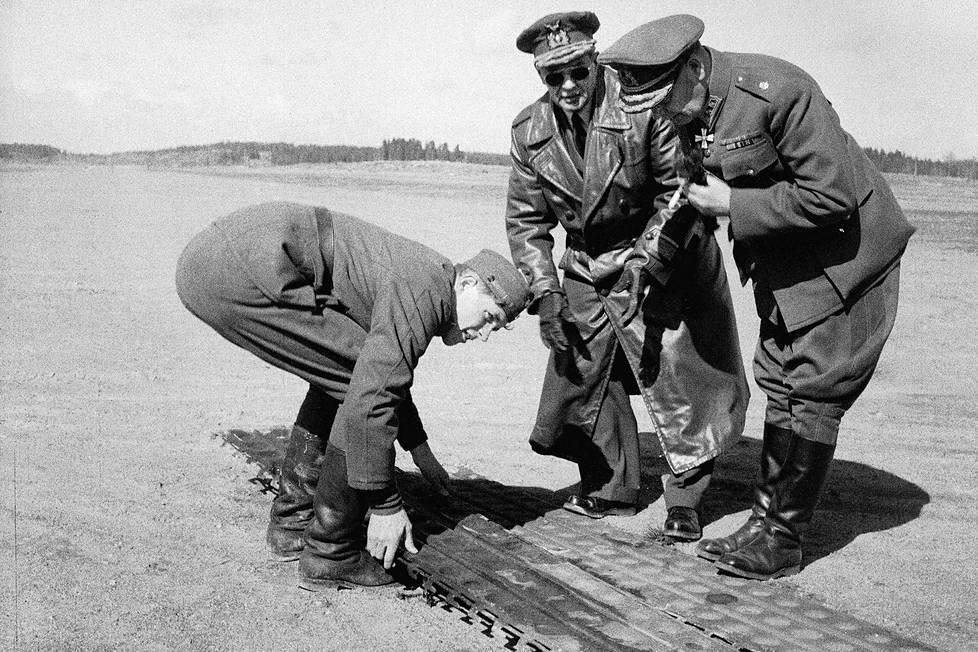 Kenraaliluutnantti E.N. Hämäläinen ja Ilmavoimien komentaja kenraalimajuri R. Artola tarkastelevat palautuksen jälkeen teräsmaton mallikappaletta. Venäläiset veivät kiitoradan matot mukanaan.