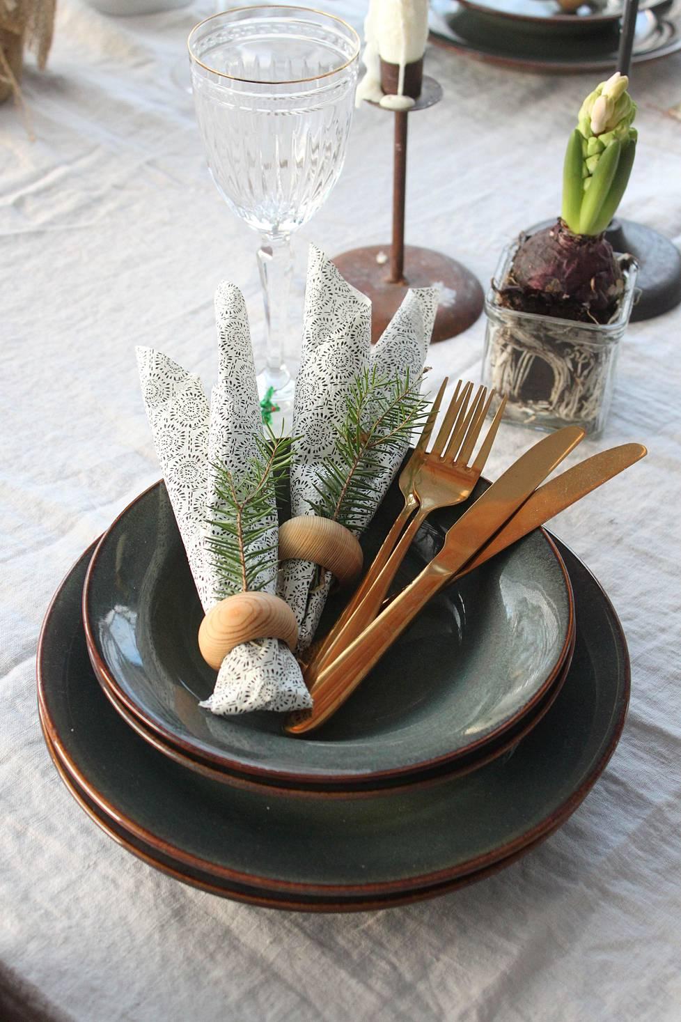 Kultaiset aterimet ja kuusenhavut ovat joulupöydän kauniita yksityiskohtia.