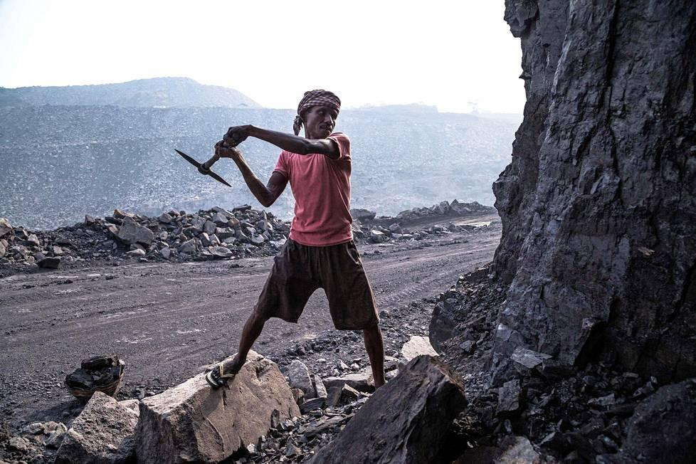 Kaivostyöläinen erotti hiiltä malmista perinteisin menetelmin, minkä jälkeen muut kuljettavat palat pois.