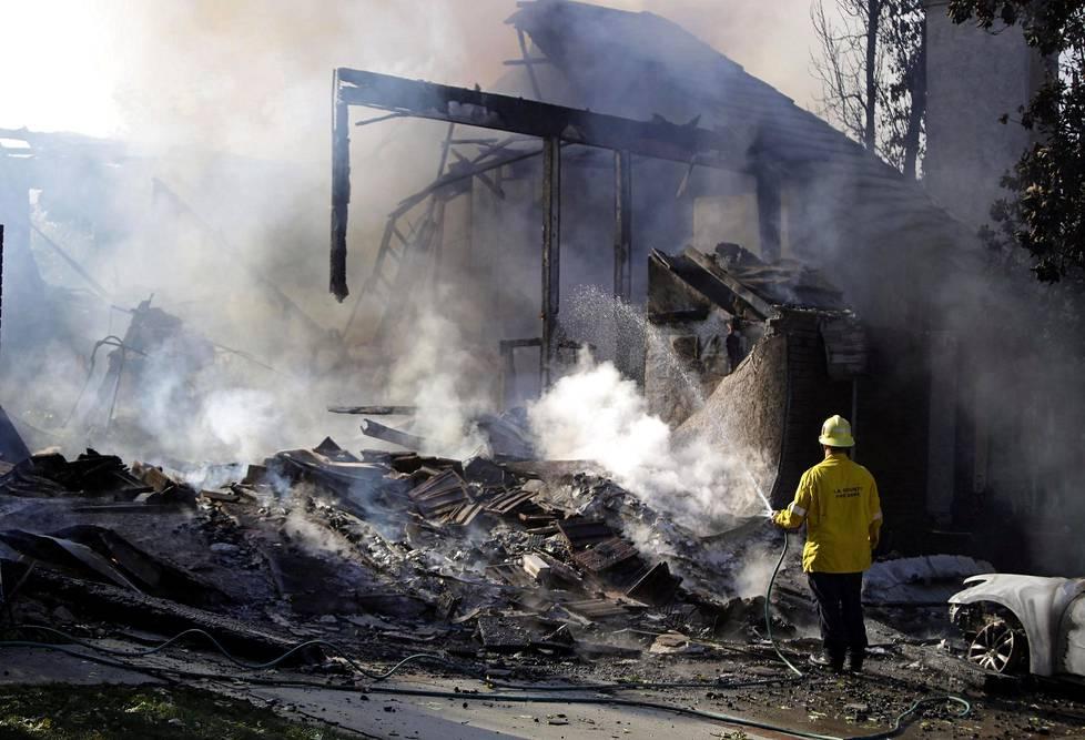 Palomies sammuttaa Woolsey Fire -palon tuhoamaa kiinteistöä Agourassa, Etelä-Kaliforniassa.